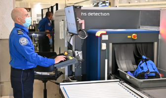 Airport news Miami International - TSA officer inspecting items using new CT technology